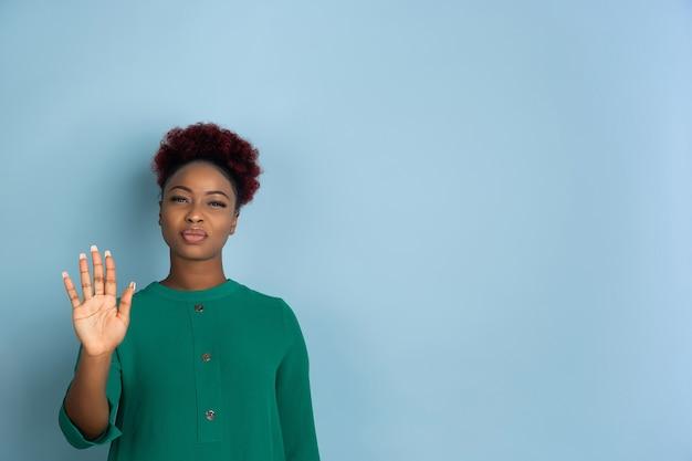Ritratto di bella donna afro-americana su sfondo blu studio