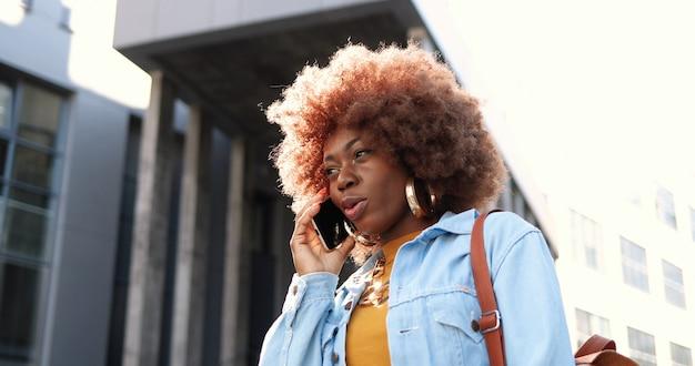 Bella donna afroamericana che parla sul telefono cellulare all'esterno. donna attraente alla moda che parla sul cellulare. conversazione telefonica.