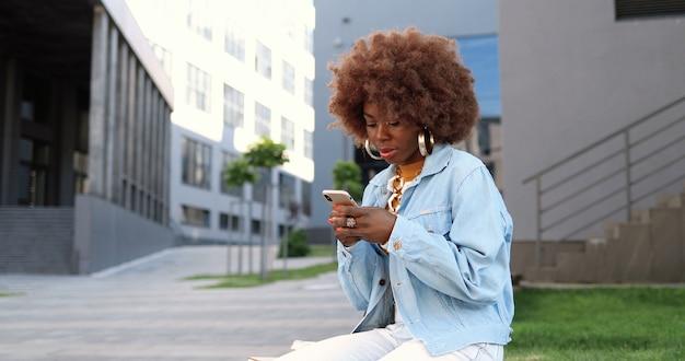 Bella donna afroamericana toccando e scorrendo sul cellulare e seduto su una panchina all'esterno. messaggistica femminile attraente alla moda sullo smartphone. chat telefonica.