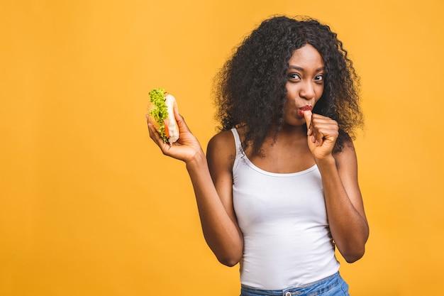 Bella giovane donna nera afroamericana che mangia hamburger