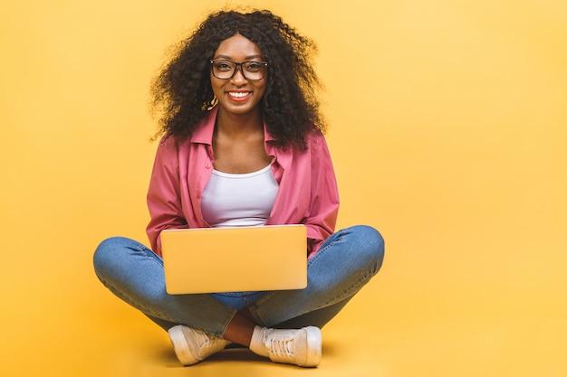 Donna di colore afroamericana in casual seduta sul pavimento nella posa del loto e tenendo il computer portatile