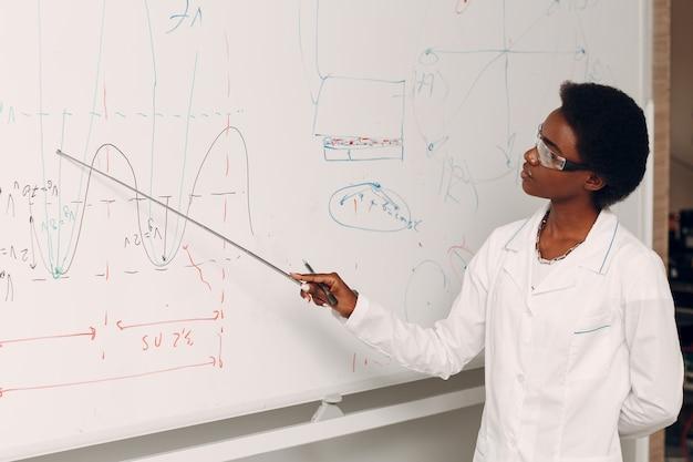 L'insegnante di matematica afroamericana della donna di colore sta al bordo bianco con il puntatore.