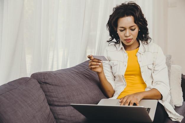 Acquisto online della donna di colore afroamericana facendo uso della carta di credito per comprare nuovo oggetto sul computer portatile durante il soggiorno a casa.