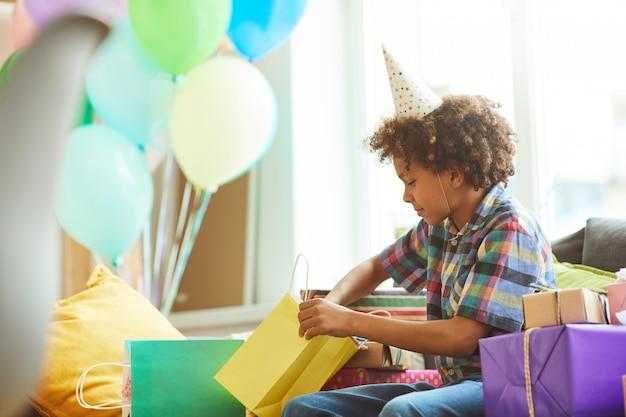 Regali di compleanno di apertura del ragazzo afroamericano