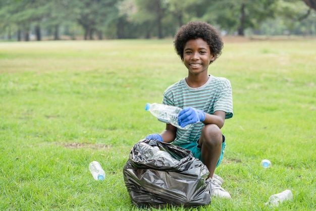 Il ragazzo volontario afroamericano che sorride raccogliendo le bottiglie di plastica in un sacchetto di immondizia nero, aiuta l'ambiente della carità della raccolta dei rifiuti