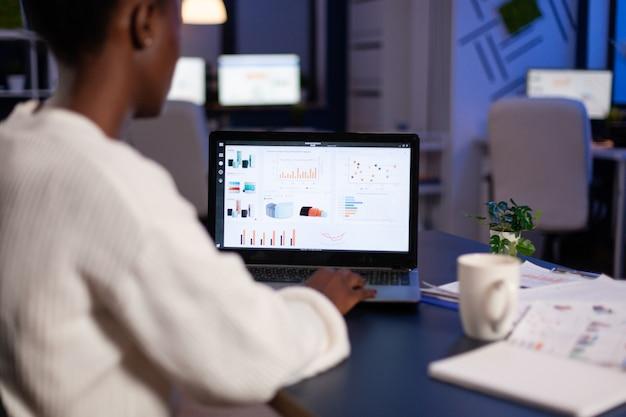 Imprenditore afroamericano che analizza i grafici delle società finanziarie