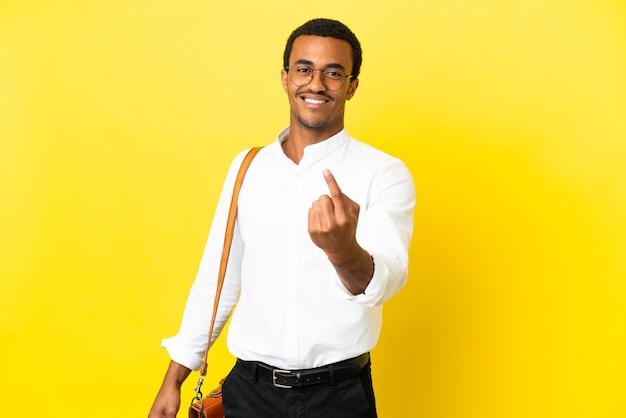Uomo d'affari afroamericano su sfondo giallo isolato facendo gesto imminente coming
