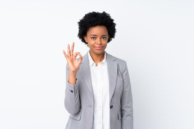 Donna afroamericana di affari sul bianco isolato che mostra un segno giusto con le dita