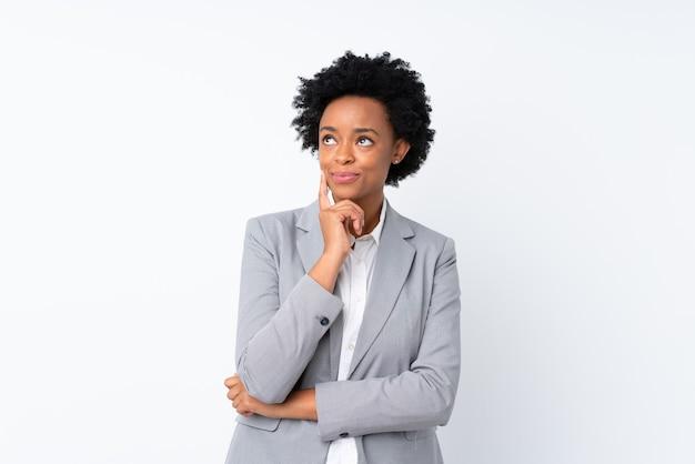 Donna afroamericana di affari sul bianco isolato che pensa un'idea