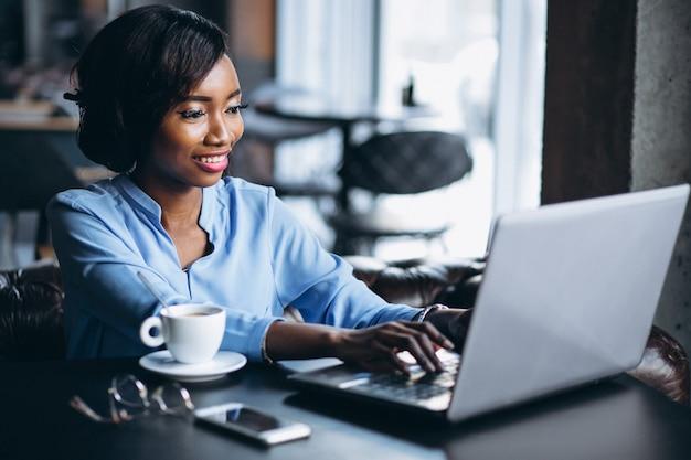 Donna afroamericana di affari con il computer portatile in un caffè