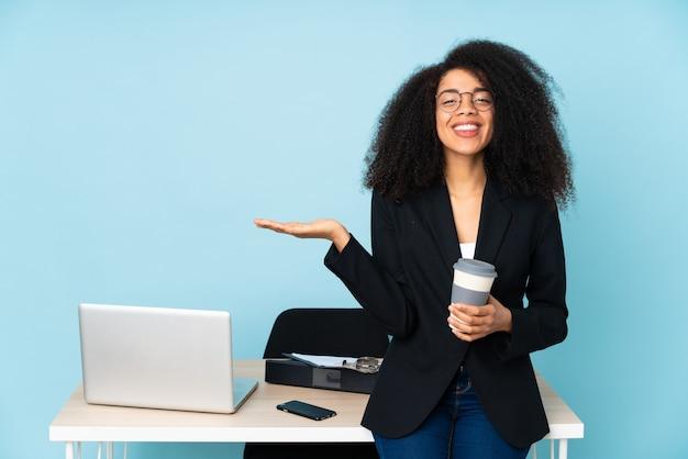 Donna afroamericana di affari che lavora nel suo posto di lavoro che tiene il copyspace immaginario sul palmo per inserire un annuncio