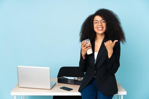 La donna afroamericana di affari che lavora nel suo posto di lavoro con i pollici aumenta il gesto e sorridente