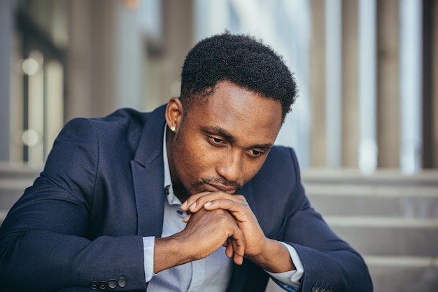 L'uomo d'affari afroamericano in giacca e cravatta frustrato ha ricevuto cattive notizie dal lavoro, licenziato depresso seduto sulle scale, foto ritratto ravvicinata
