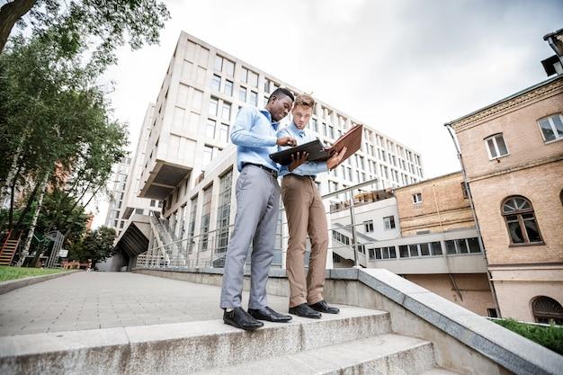 Uomo d'affari afroamericano e un uomo d'affari caucasico discutendo e guardando i documenti sulla città