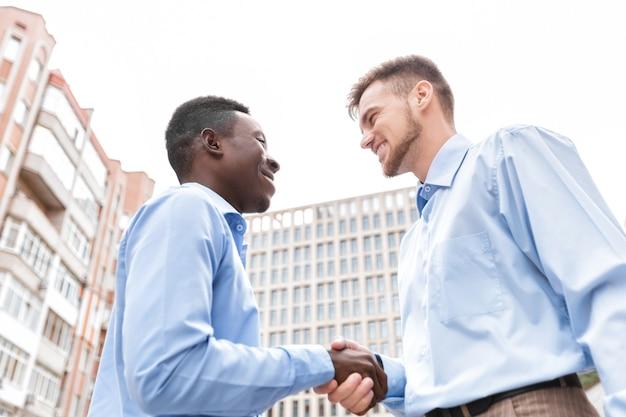 Uomo d'affari afroamericano e un uomo d'affari caucasico che agitano le mani sugli edifici della città, vista dal basso