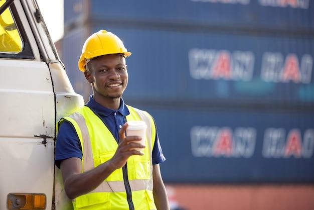 Uomo d'affari afroamericano che beve caffè, uomo nero ha una pausa caffè al contenitore all'aperto di cantiere