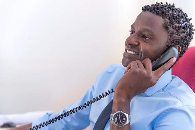 Uomo d'affari afroamericano al telefono seduto al computer nel suo ufficio