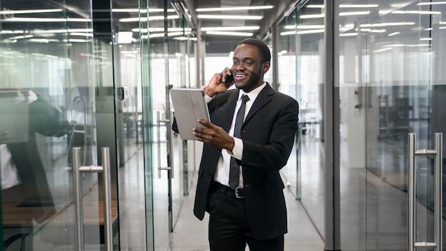 Uomo d'affari afroamericano che parla sullo smartphone mentre camminando nell'edificio per uffici corporativo e controllando i messaggi di posta elettronica online al pc della compressa. concetto di uomo d'affari di successo.