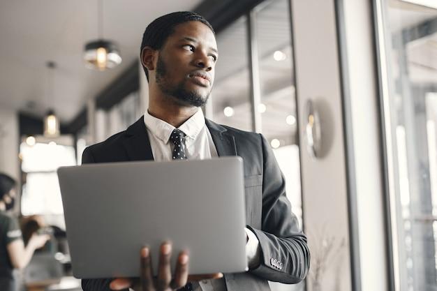 Uomo d'affari afroamericano che utilizza un computer portatile in un caffè.