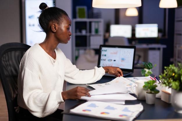 Donna d'affari afroamericana che controlla i documenti aziendali che lavorano in modo eccessivo alla strategia finanziaria