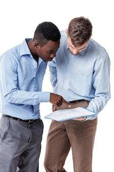 Uomo d'affari afroamericano e caucasico che esamina i documenti e che discute il contratto su un bianco