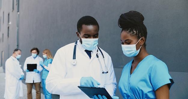Coppia afroamericana dell'uomo e della donna, colleghi medici in maschere mediche lavorando e utilizzando il dispositivo tablet. medici maschii e femmine che parlano, toccano e scorrono sul computer del gadget.
