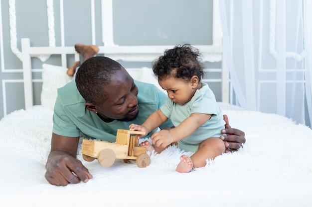 Papà afroamericano con figlio bambino che gioca sul letto di casa con una macchinina in legno, famiglia felice, festa del papà