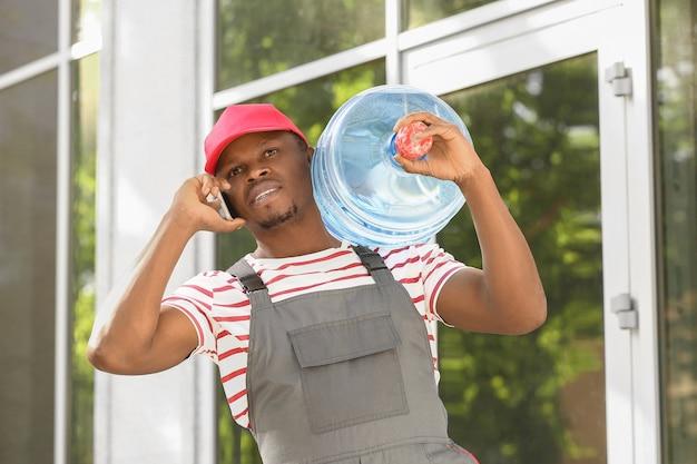 Fattorino afroamericano con una bottiglia d'acqua che parla al cellulare all'aperto