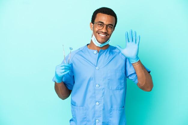 Dentista afroamericano che tiene gli strumenti su sfondo blu isolato salutando con la mano con espressione felice