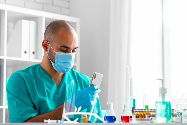 Medico afroamericano o lavoratore di laboratorio utilizzando il suo smartphone al posto di lavoro si chiuda