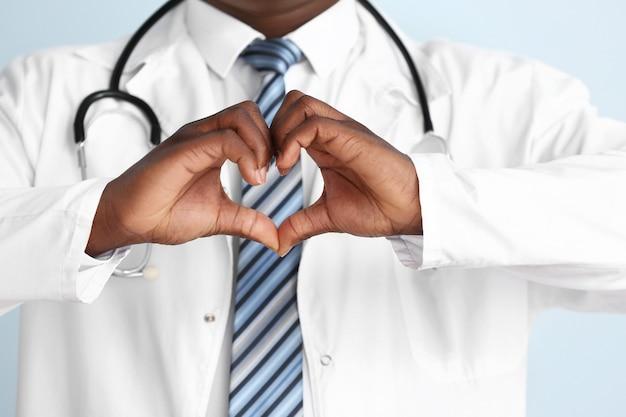 Medico afro-americano che fa il cuore con le sue mani, primo piano