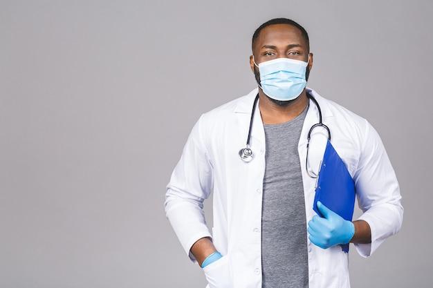Uomo di medico afroamericano in guanti di maschera facciale. tenendo appunti. Foto Premium