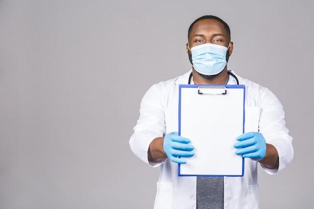 Uomo di medico afroamericano in guanti di maschera facciale. tenendo appunti.