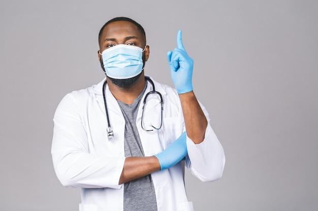 Uomo afroamericano medico in guanti maschera sterile abito medico. dito puntato.