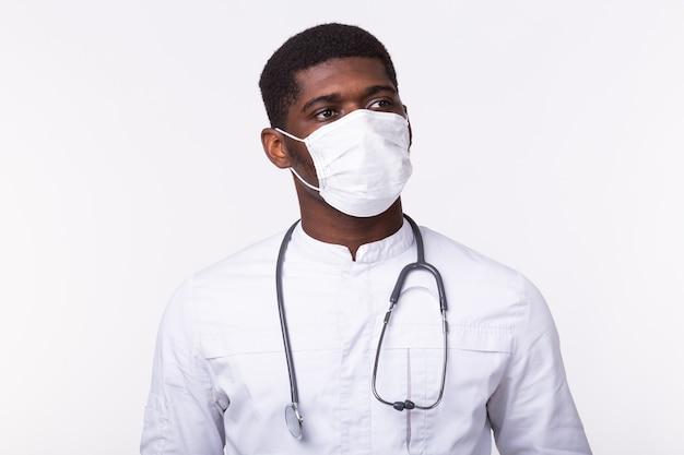 Medico afroamericano in una maschera sopra il muro bianco. concetto di medicina, sanità e persone.