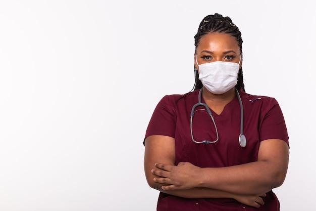 Medico afroamericano in una mascherina medica sopra il muro bianco con lo spazio della copia. medicinale