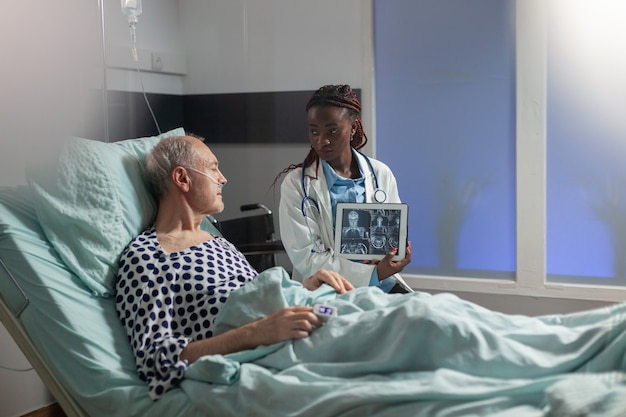 Medico afroamericano seduto accanto a un uomo anziano che spiega un trauma corporeo