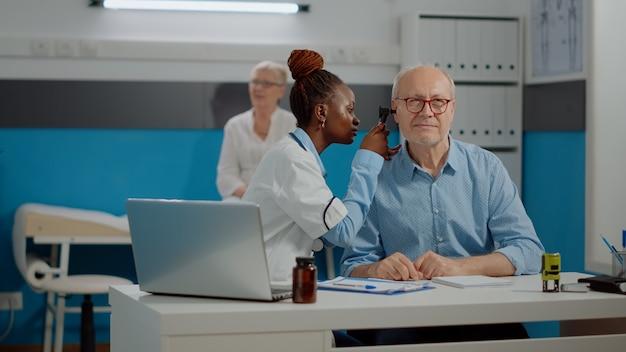 Medico afroamericano che utilizza l'otoscopio che consulta l'uomo più anziano con la malattia in gabinetto medico. otologo nero che fa l'esame dell'orecchio con uno strumento professionale su un paziente anziano alla scrivania