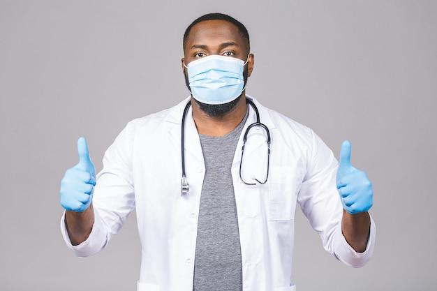 Medico afroamericano che indossa guanti e maschera medica. pollice su.
