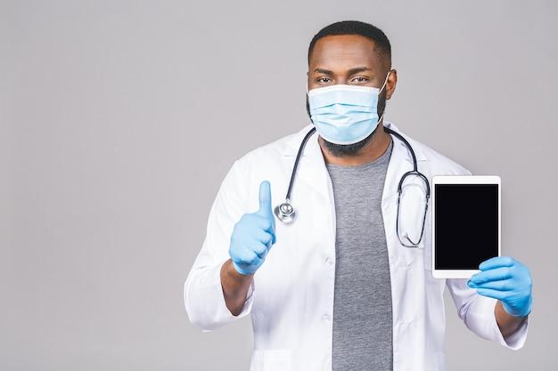 Medico afroamericano che indossa maschera protettiva igiene chirurgica e tenendo in mano il computer tablet