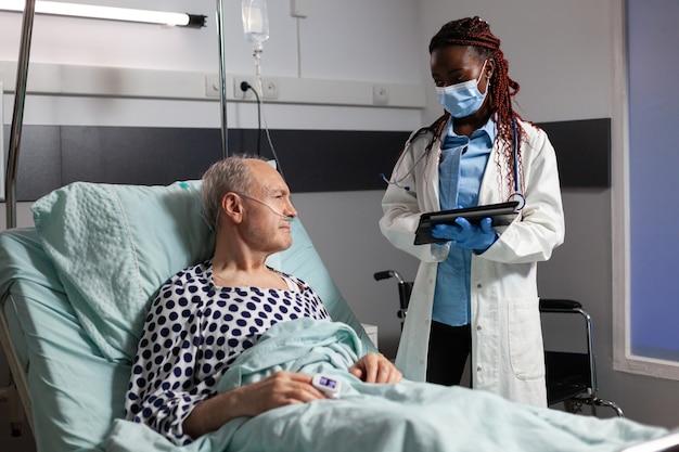 Medico afroamericano con maschera chirurgica nella stanza d'ospedale che discute diagnosi
