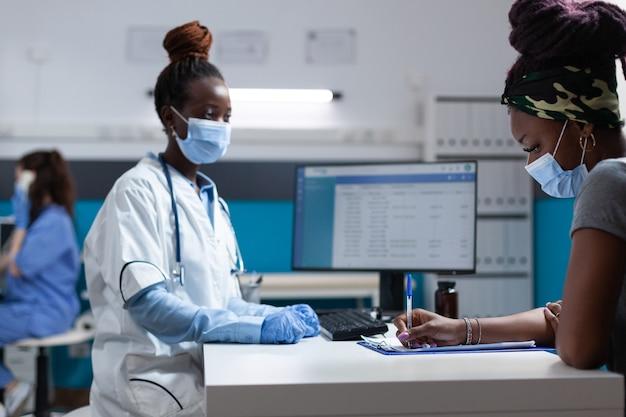 Medico afroamericano con maschera protettiva che spiega il trattamento farmacologico