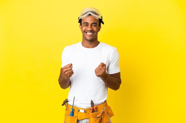 Elettricista afroamericano sopra la parete gialla isolata che celebra una vittoria nella posizione del vincitore