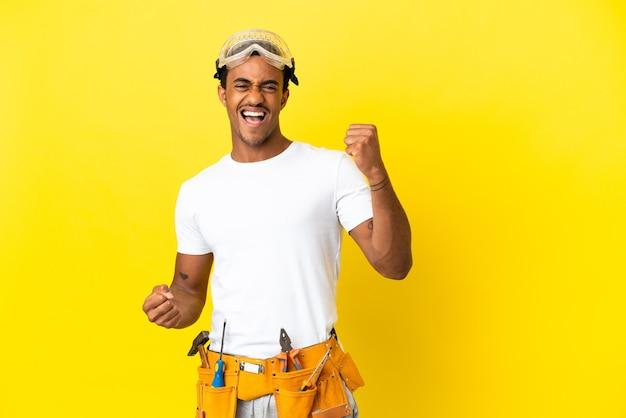 Elettricista afroamericano sopra il muro giallo isolato che celebra una vittoria