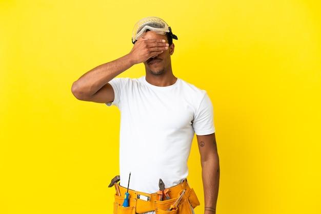 Uomo dell'elettricista afroamericano sopra gli occhi gialli isolati del rivestimento murale a mano. non voglio vedere qualcosa