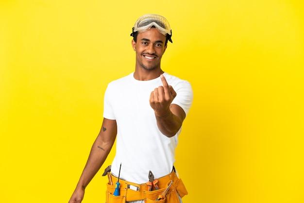 Uomo dell'elettricista afroamericano sopra la parete gialla isolata che fa il gesto venente