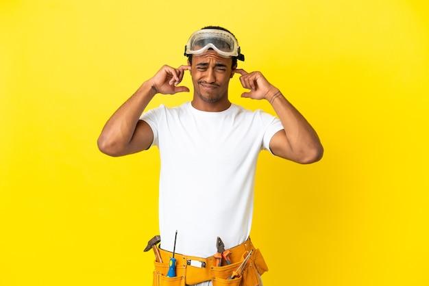 Elettricista afroamericano sopra un muro giallo isolato frustrato e che copre le orecchie