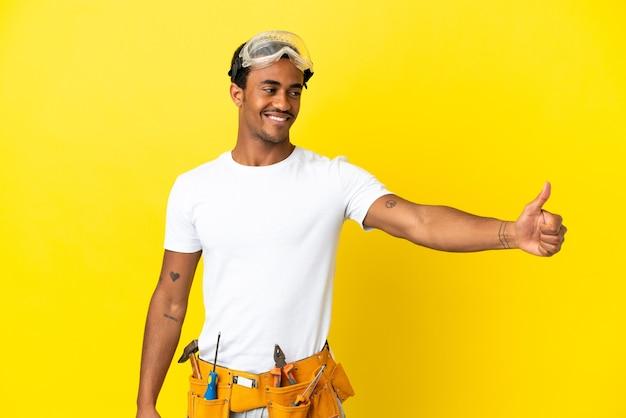 Elettricista afroamericano sopra la parete gialla isolata che dà un gesto di pollice in alto