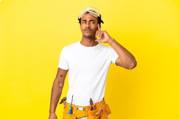 Elettricista afroamericano sopra il muro giallo isolato con dubbi e pensieri