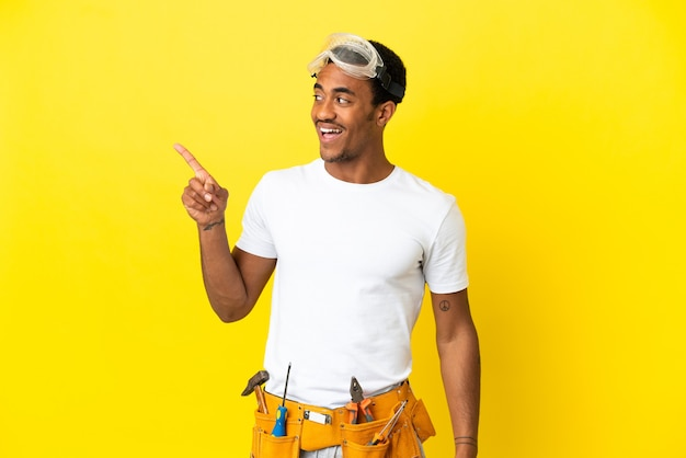 L'elettricista afroamericano sopra il muro giallo isolato con l'intenzione di realizzare la soluzione sollevando un dito